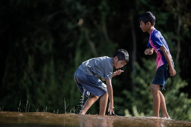 Asiatische kinder, die in einem fluss spielen