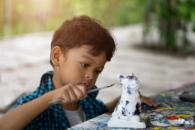 Asiatische kinder, die seine malerei mit malerpinsel genießen