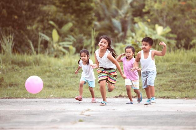 Asiatische kinder, die spaß haben, auf dem gebiet zusammen zu laufen und zu spielen