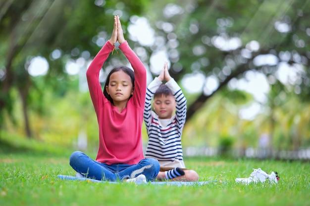 Asiatische kinder, die yogahaltung im park im freien tun