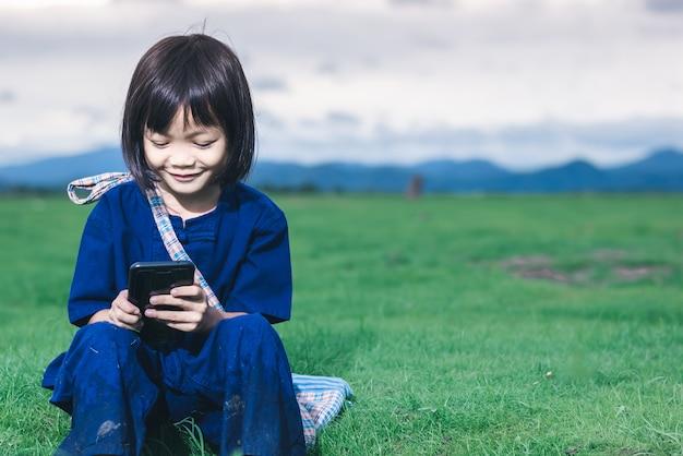 Asiatische kinder im lokalen kleid benutzen intelligentes telefon für bildung und kommunikation an der landschaft von thailand.