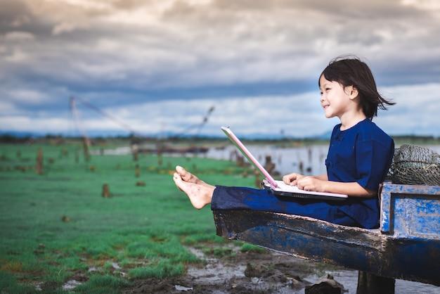 Asiatische kinder im lokalen kleid benutzen laptop für bildung und kommunikation an der landschaft von thailand.