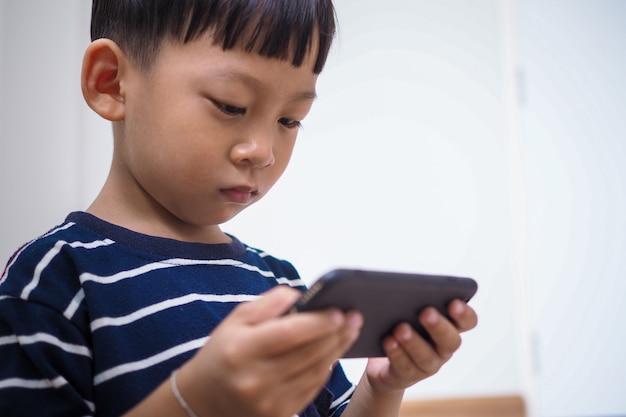 Asiatische kinder im zeitalter sozialer netzwerke, die sich auf telefone oder tablets konzentrieren