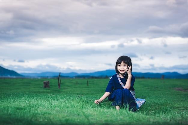 Asiatische kinder in lokaler kleidung benutzen das smartphone, das seine mutter anruft, um sie am feld abzuholen, nachdem sie fertig gefischt haben