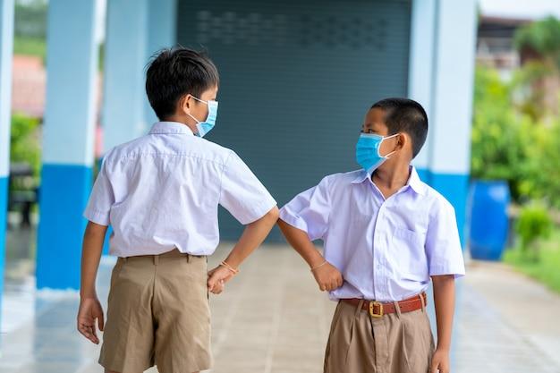 Asiatische kinder in schuluniform, die eine schutzmaske tragen, um sich gegen covid-19 zu schützen, schütteln sich gegenseitig die ellbogen, grüßen sich gegenseitig, begrüßen den ellbogen, verhindern coronaviren und distanzieren sich sozial.