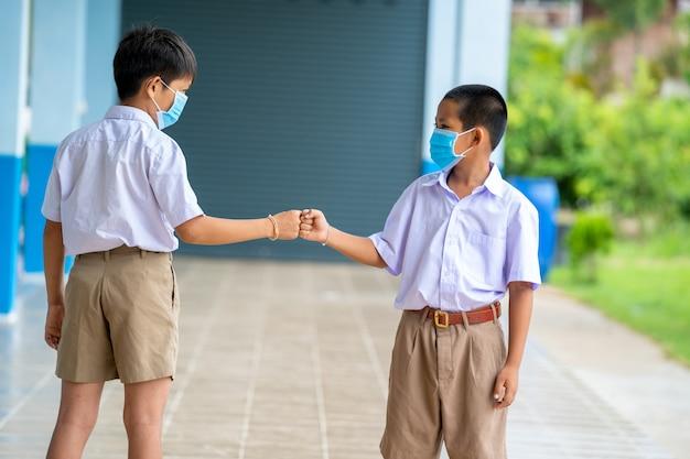 Asiatische kinder in schuluniform mit schutzmaske zum schutz vor covid-19 in schuluniform in der grundschule. sie grüßen sich mit sozialer distanz. neue normalität.