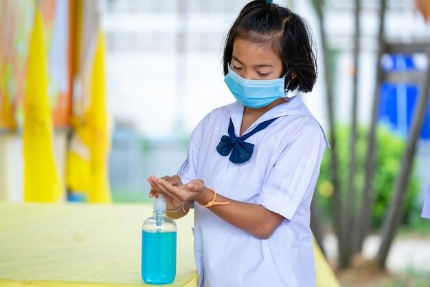 Asiatische kinder in schuluniform mit schutzmaske zum schutz vor covid-19, prävention gegen covid-19 in der grundschule, bildung, grundschule, lernen und menschenkonzept.