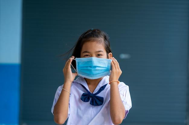 Asiatische kinder in schuluniform mit schutzmaske zum schutz vor covid-19, zurück in die schule für ein neues normales lebensstilkonzept.
