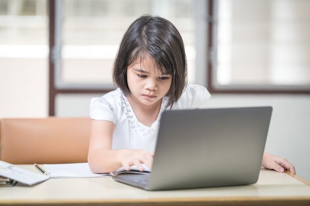 Asiatische kinder mädchen studentin schreiben auf notebook beim online-studium über laptop zu hause. bildungskonzept stockfoto