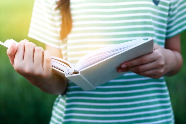 Asiatische kinder öffnen ein weißes buch, um zu lernen und zu lernen.