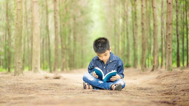 Asiatische kinder sind entspannende lesung im garten bildungs- und leutekonzept zurück zu schule