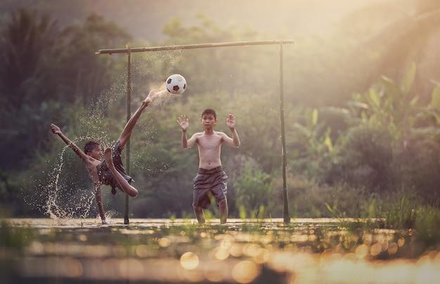 Asiatische kinder spielen fußball im fluss, thailand-landschaft