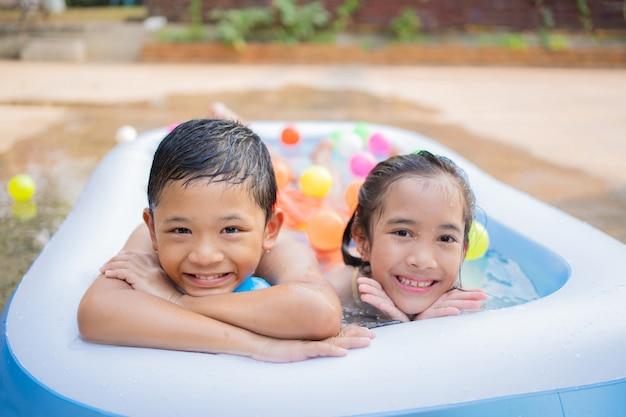 Asiatische kinder spielen im sommer in einem kleinen schwimmbad