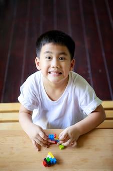 Asiatische kinder spielen kinderspielzeug zu hause wohnzimmer