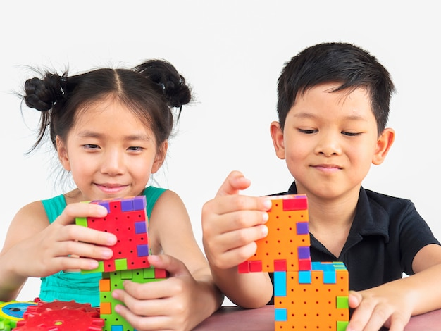 Asiatische kinder spielen kreatives spiel des puzzle-plastikblocks