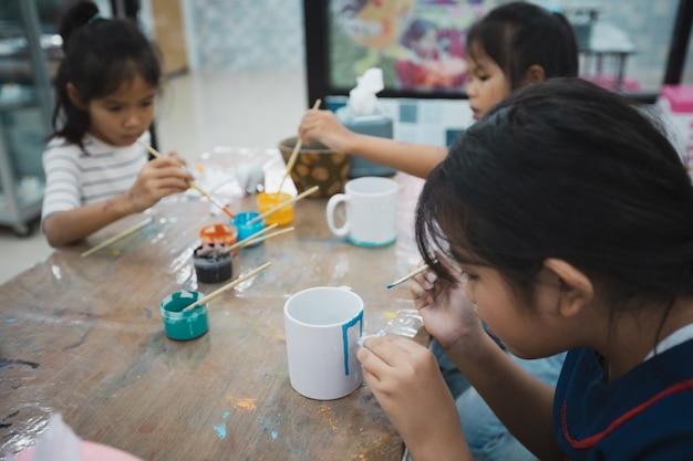 Asiatische kinder und freunde konzentrieren sich darauf, mit spaß zusammen mit öl auf keramikglas mit ölfarbe zu malen. kreative aktivitätsklasse für kinder in der schule.