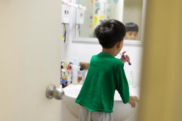 Asiatische kindergartenkinder üben das zähneputzen zu hause selbst im badezimmer.