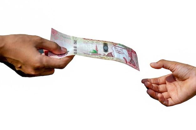 Asiatische kinderhand mit 100 riyal, der währung saudi-arabiens, konzept des gebens. flacher fokus und isoliert auf weißem hintergrund