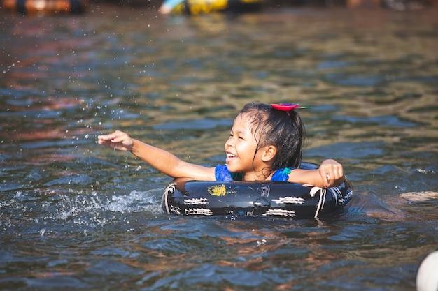 Asiatische kindermädchen, die wasser mit aufblasbarem ring im fluss in der sommerzeit spielen