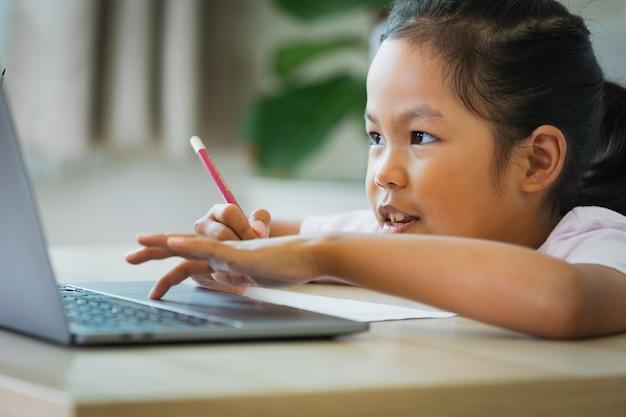 Asiatische kindermädchen studieren online mit dem lehrer per videoanruf. das kind unterrichtet während der quarantäne aufgrund der covid-19-pandemie mit computer-laptop.