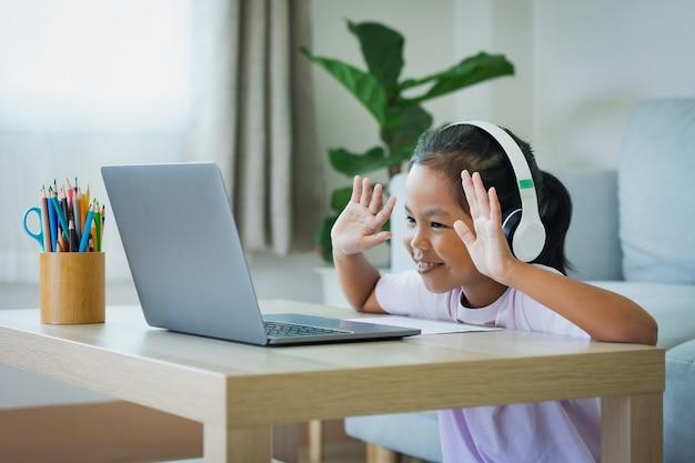 Asiatische kindermädchen tragen kopfhörer online mit dem lehrer per videoanruf. das kind unterrichtet während der quarantäne aufgrund der covid-19-pandemie mit computer-laptop.