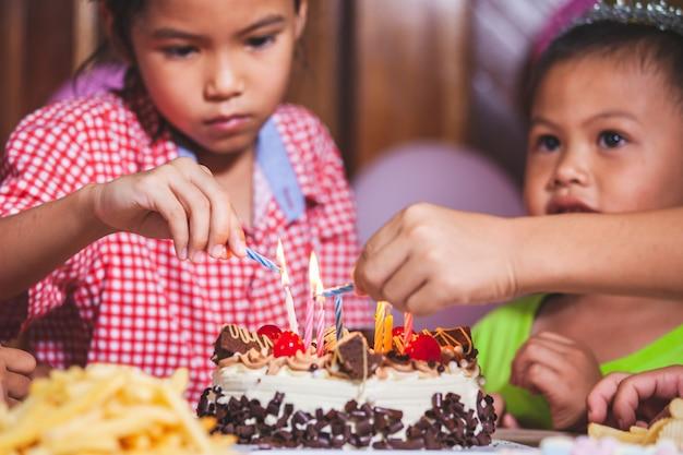 Asiatische kindermädchen und -jungen, die kerze auf geburtstagstorte zusammen in der geburtstagsfeier anzünden