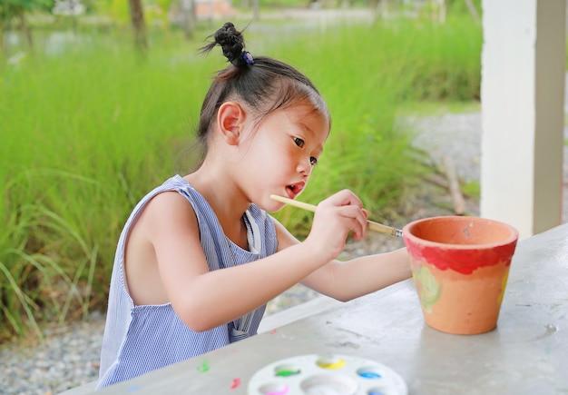Asiatische kindermädchenfarbe auf töpferwarenteller.