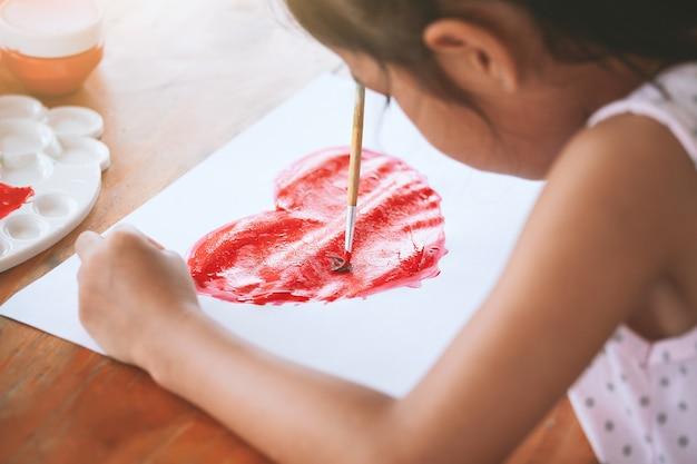 Asiatische kinderzeichnung und malte ein herz für die karte des valentinsgrußes mit spaß und glück