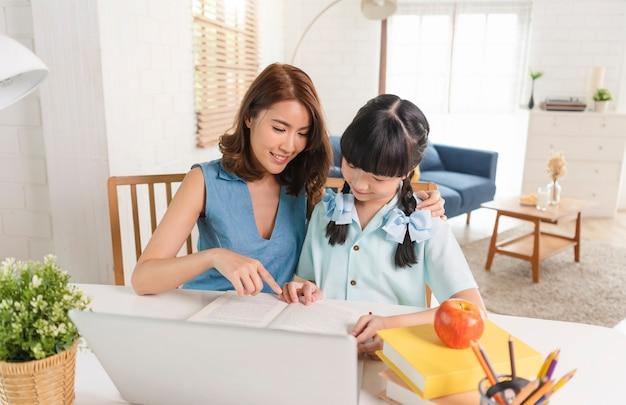 Asiatische kleine junge studentin der schule, die lernt, auf tisch zu sitzen und mit seiner mutter zu hause arbeitet.