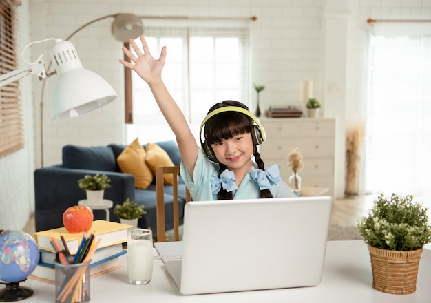 Asiatische kleine junge studentin homeschool, die virtuelle internet-online-klasse auf tisch zu hause lernt.