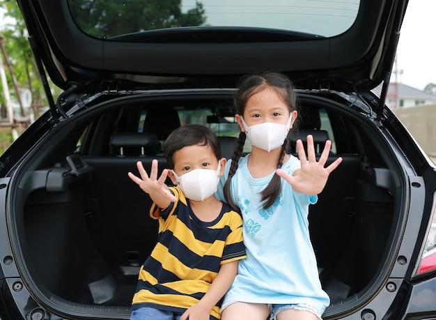 Asiatische kleine jungen und mädchen tragen eine hygiene-gesichtsmaske und eine hand-stop-schild-geste, die auf einem schrägheck-auto sitzt und während des ausbruchs des coronavirus (covid-19) durch die kamera schaut