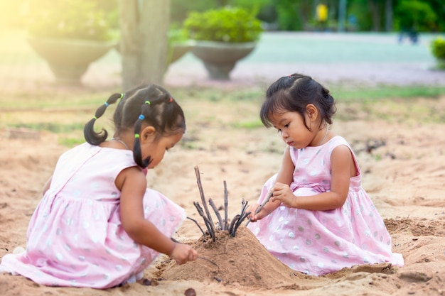 Asiatische kleine mädchen des kindes zwei, die zusammen mit sand im spielplatz spielen