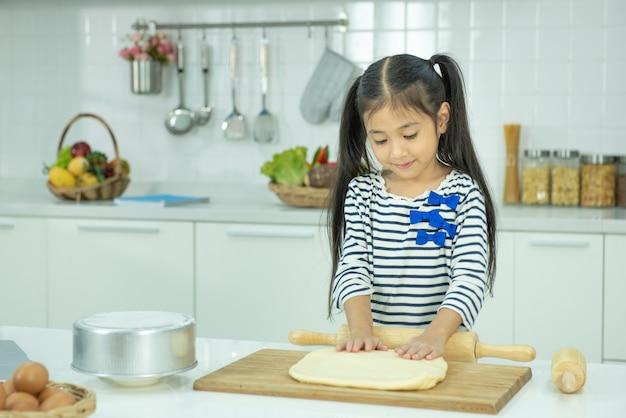 Asiatische kleine mädchenkoch rollt den teig für pizza mit einem hölzernen nudelholz auf einem schwarzen tisch, der mit mehl bestreut wird.