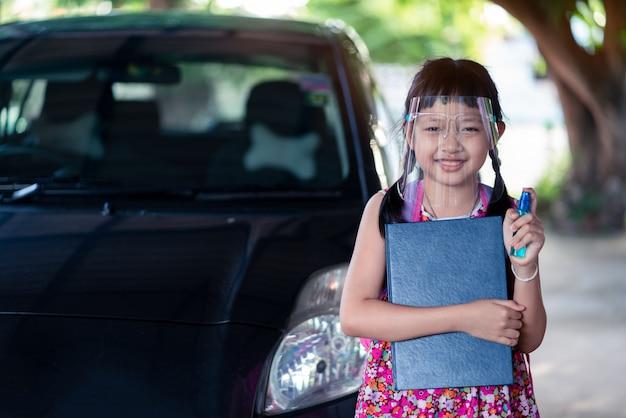 Asiatische kleine studentin, die gesichtsschutz trägt, während sie nach covid-19-quarantäne zurück zur schule geht.