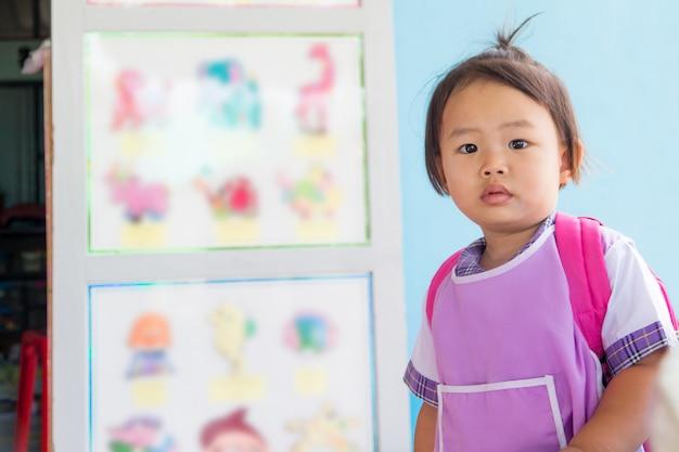 Asiatische kleine vorschulstudentin in der allgemeinen uniform und in der roten tasche, die zur schule geht