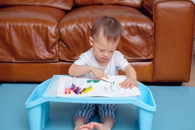 Asiatische kleinkindjungenzeichnung, kritzelnd mit buntem hersteller