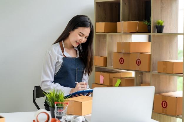 Asiatische kleinunternehmerin, die produkte online zur kenntnis nimmt, bevor sie sie mit paketkasten zu hause an kunden ausliefert.