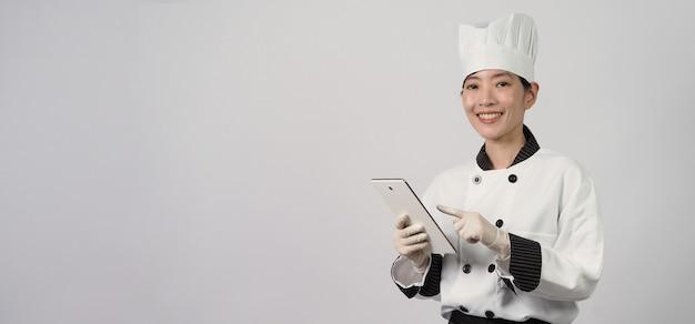 Asiatische köchin, die smartphone oder digitales tablet hält und essensbestellung vom online-shop erhalten hat