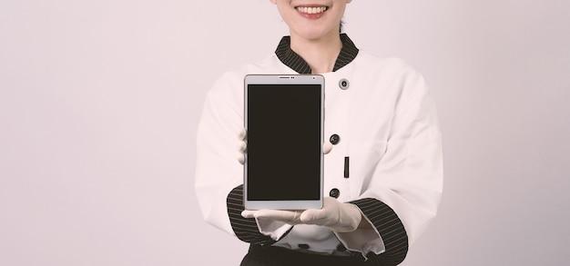 Asiatische köchin mittleren alters, die ein smartphone oder ein digitales tablet hält und eine online-bestellung erhalten hat