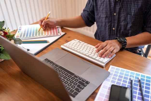 Asiatische kollegedesigner-zeichnungsskizzen auf grafischem laptop.