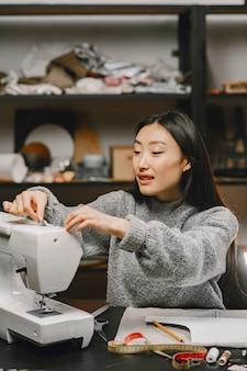 Asiatische koreanische frau schneiderin in der näherin werkstatt arbeiten