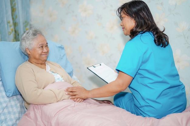 Asiatische krankenschwesterdoktorsorgfalt, hilfe und älterer frauenpatient der unterstützung legen sich im bett am krankenhaus hin.