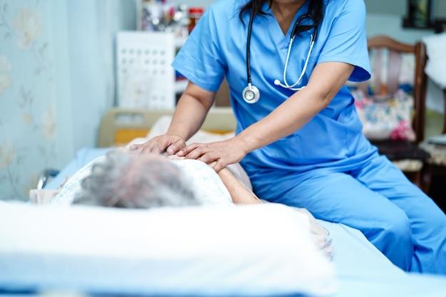 Asiatische krankenschwesterphysiotherapeut-doktorsorgfalt, -hilfe und -unterstützung älterer oder älterer frauenpatient alter dame legen sich im bett an der krankenstation hin