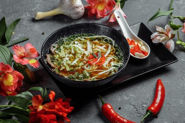 Asiatische küche, rindfleischsuppe für einen schwarzen teller auf einem dunklen.