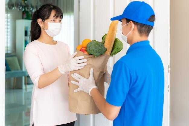 Asiatische kundin, die gesichtsmaske und handschuh trägt, erhalten lebensmittelschachtel mit lebensmitteln, obst, gemüse.
