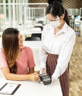 Asiatische kundin macht kontaktlose kreditkartenzahlung nach dem essen in einem neuen normalen sozialen distanzrestaurant, um berührungen zu reduzieren. online kontaktloses und technologisches konzept.