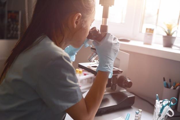 Asiatische laborassistentin schaut in das mikroskop bei der probe, die in der nähe des fensters im krankenhaus sitzt