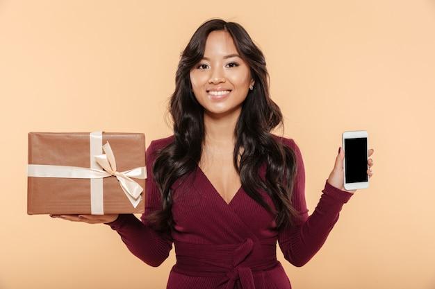 Asiatische lächelnde frau im kastanienbraunen kleid, das präsentkarton mit smartphone als geschenk lokalisiert über pfirsichhintergrund demonstriert