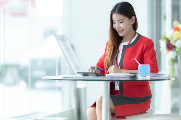 Asiatische lächelnde geschäftsfrau in der klage sprechend am telefon unter verwendung der tablette, die am büro workpl sitzt