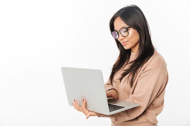 Asiatische lächelnde tragende gläser der frau unter verwendung des laptops